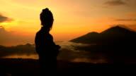 Girl watching sunrise over Lake Batur, Volcano Agung and Abang, Bali, Indonesia video