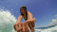 Girl waving and smiling into the camera while surfing video