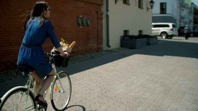 Girl wearing sunglasses with waving dark hair cycling near buildings. Cars parked near the road, slow mo, stedicam shot video