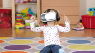Girl wearing virtual reality goggles. Virtual reality game. The little girl with surprise and pleasure uses head-mounted display. video