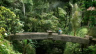 Girl with a bandage on his head and selfie stick in hand goes through the old stone bridge in the tropical jungle. Tourist walking to exotic places in the resort video