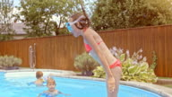 SLO MO PAN Girl with swimming mask jumping into pool video