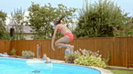 SLO MO Girl with mask jumping into pool with splash video
