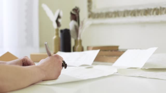 Girl with beautiful hands writing a letter at the table video