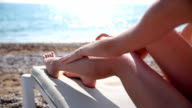 Girl with beautiful legs applying sunscreen on a sea background. video
