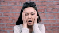 Girl with black long hair depict shock, surprise in camera. Casting. Brick wall video