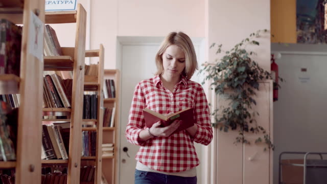 Girl with book walking down the library video