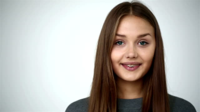 Girl with braces on teeth looking at camera and smiling. video