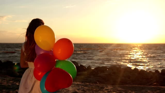 Girl with colorful balloons on beach at sunset video