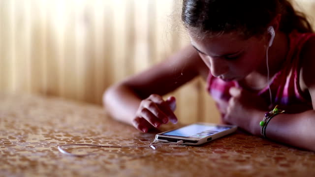 Girl with earphones looks web pages on his smartphone video