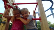 Girl with ears and glasses and boy with white hair having fun on the children's tower. video