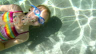 Girl with goggles swimming in pool waving under water video