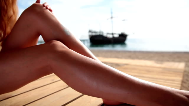 Girl with gorgeous long legs applying sunscreen on a sea background. video