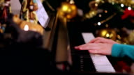 Girl with green playing piano near Christmas tree video