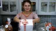 Girl with hair tucked away in a ponytail, wearing a light t-shirt is holding cute looking at the camera , white box. In the background, bright kitchen with sweets on the table video
