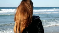 Girl with long red hair on the beach video