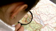 girl with magnifier studies a map of Europe. video