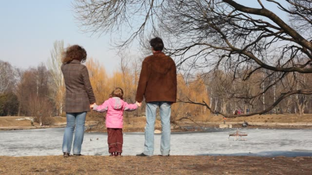 Girl with parent looks at pond video