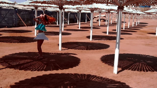 girl with red hair and glasses is spinning in the shade of a parasol around herself in slow motion video