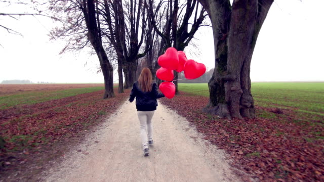 Girl with red heart shaped balloons running in park video