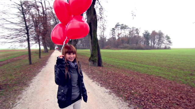 Girl with red heart shaped balloons waiting in park video