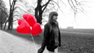 Girl with red heart shaped balloons walking in park video