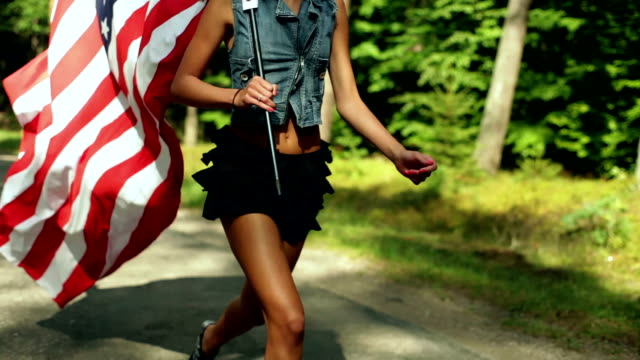 Girl with slim legs running among the trees with the american flag. video