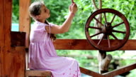 Girl with smartphone sits near wooden wheel video