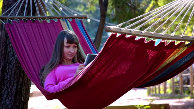 Girl with tablet pc on hammock video