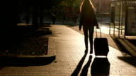 Girl with trolley suitcase come along empty pavement, silhouette view video
