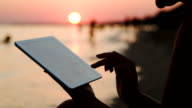 Girl working with tablet PC on beach at sunset video