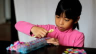 Girl Works On Colorful Bracelet On With Her Loom video