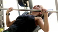 A girl works out in the gym lifting the barbell training breast muscles video