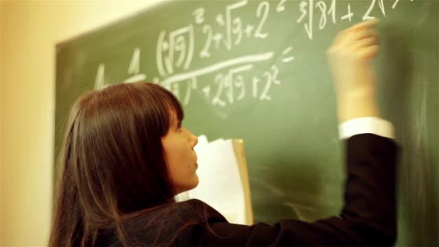 girl writing mathematical equation on chalkboard video