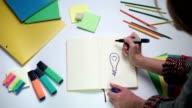 Girl writing word idea on notepad above lightbulb video