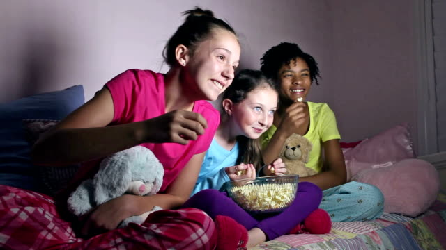 Girlfriends at sleepover eating popcorn watching TV video