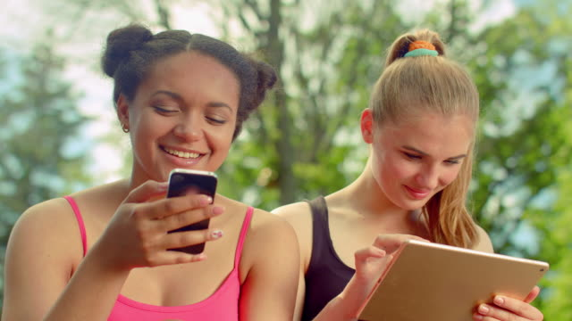 Girlfriends smiling together when chatting in social networks video