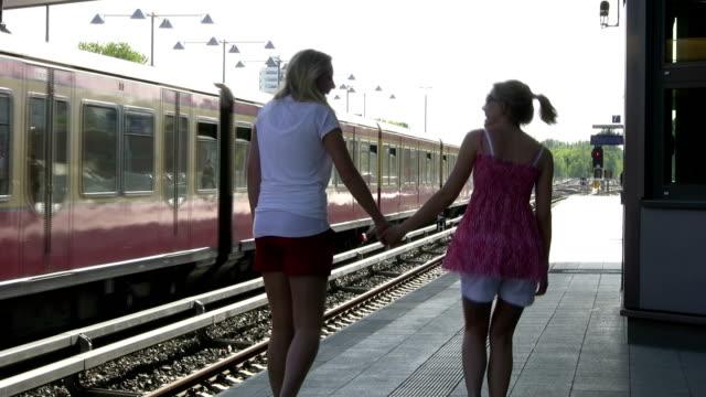 Girlfriends walking on train platform video