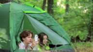 Girls and the little boy admire the nature lying in tent video