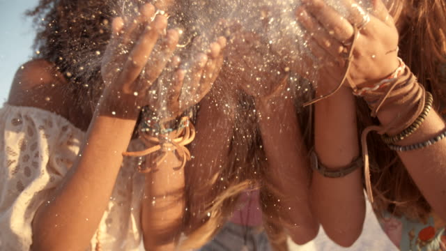 Girls blowing confetti from hands on beach in Slow Motion video