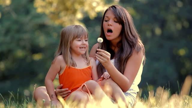 Girls Blowing Dandelion Seeds In the Park video