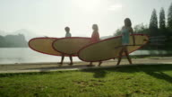 SLOW MOTION: Girls carrying SUP boards by the lake video