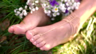 Girl's feet in grass with fresh flowers and gold jewellery video