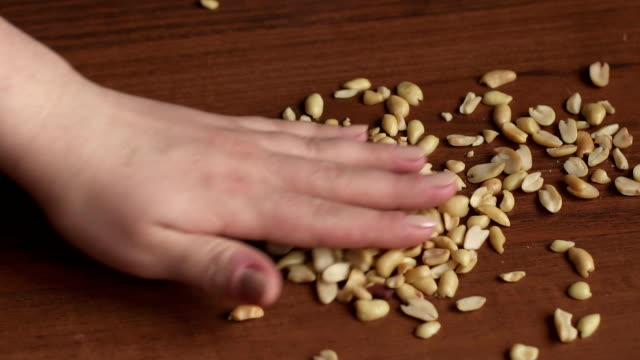 Girl's hand holds handful of nuts on table, cu video