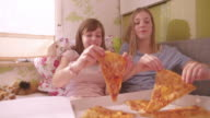 Girls holding cheesy slices of pizza in front of faces video