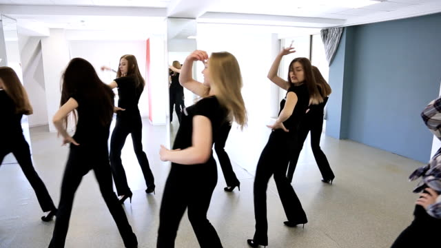 Girls in black uniform actively dance in class on lesson of choreography video