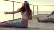 Girls in bright leggings professionally dancing modern dance on a wooden pier near the sea at sunset video