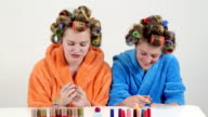 Girls in hair curlers having fun with colorful nail polishes painting nails video