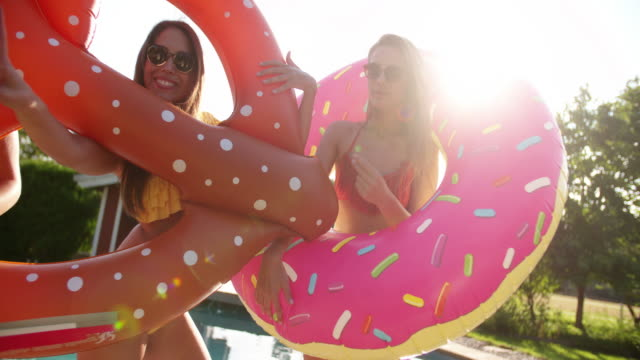 Girls joking around with novelty pool inflatables with sunflare video