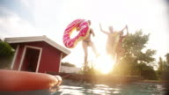 Girls jumping into a swimming pool on summer evening video